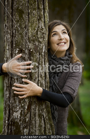 Hugging a tree stock photo, Portrait of a beautiful young woman hugging a tree in fall season by ikostudio