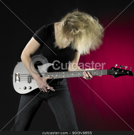playing bass guitar stock photo, a woman playing a black bass guitar in front of partly reddish back by prill