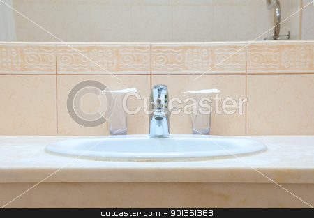 Hotel bathroom stock photo, White sink, chrome tap and two glasses in a hotel bathroom by Iryna Rasko