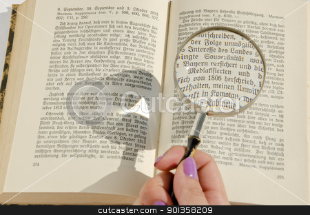 Woman's hand holding magnifying glass over the german book page. stock photo, Woman's hand holding magnifying glass over the german book page. Enlarged text detail. by sauletas