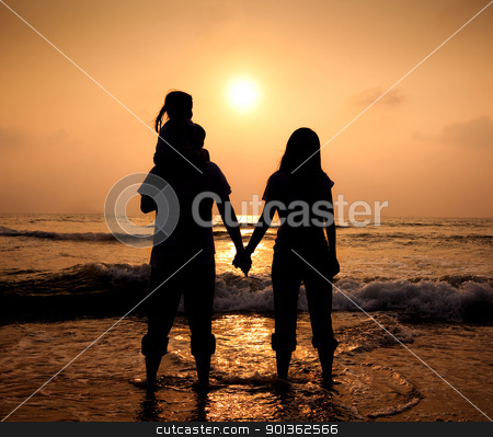 The silhouette of loving asian family walking while holding hands on beach at sunset stock photo, The silhouette of loving asian family walking while holding hands on beach at sunset by tomwang