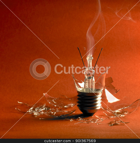 broken light bulb stock photo, broken upright light bulb with smoke and lots of shards in orange red back by prill