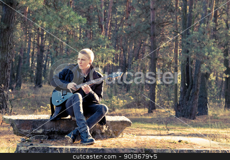 musician stock photo, teen musician plays the guitar in the autumn forest by Salauyou Yury
