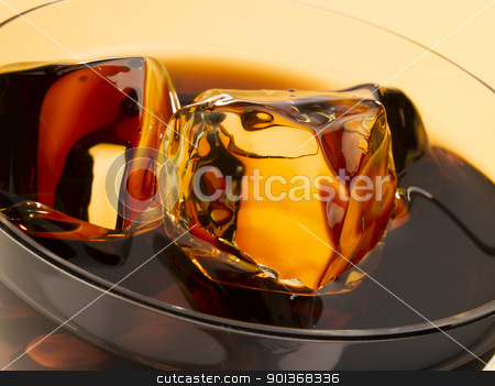 Ice cubes in cola stock photo, Close up of ice cubes floating in a glass of cola by Han van Vonno