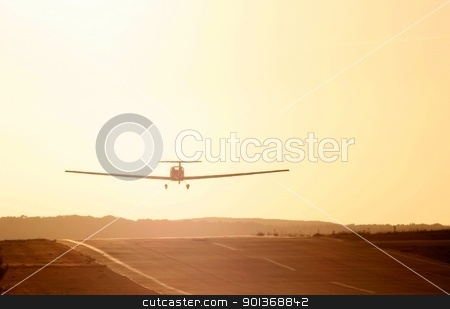 Light aircraft taking off stock photo, Light aircraft taking off into sunset by steve ball