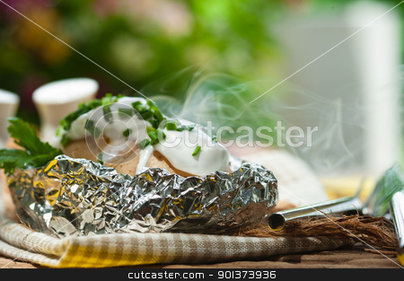 Outdoor photo of an baked potato in a aluminum-foil stock photo, Outdoor photo of an baked potato in a aluminum-foil by p.studio66