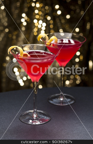 Cosmopolitan cocktail with lemon garnish stock photo, Cosmopolitan cocktail with lemon garnish in front of a gold glitter background by Ulrich Schade