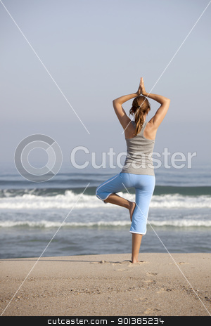 Yoga time stock photo, Beautiful young woman on the beach doing yoga exercises by ikostudio