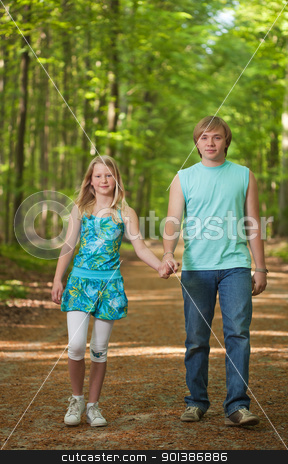 Children walking together stock photo, Teenager brother and sister walking along the path in the woods  by Mikhail Lavrenov
