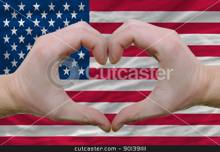 Heart and love gesture showed by hands over flag of usa backgrou stock photo, Gesture made by hands showing symbol of heart and love over american flag by Vedran Vukoja 
