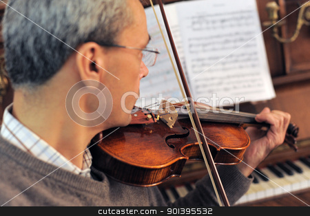 violinist stock photo, violinist with piano in the background, focus on the violin by Bonzami Emmanuelle
