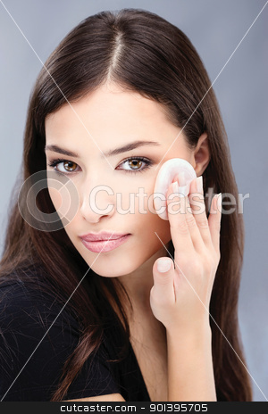 pretty black hair woman applying make up on her cheek stock photo, pretty woman applying make up with cosmetic sponge by iMarin