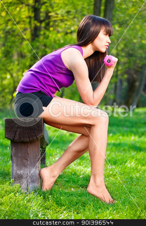 woman doing fitness exercises outdoors stock photo, Young brunette woman doing fitness exercises outdoors by iMarin