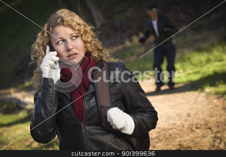 Pretty Young Teen Girl Walking with Man Lurking Behind Her stock photo, Pretty Young Teen Girl Calling on Cell Phone with Mysterious Strange Man Lurking Behind Her. by Andy Dean