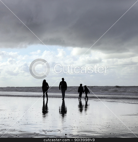happy family strolling along beach stock photo, happy family strolling along beach and children holding hands by anton havelaar