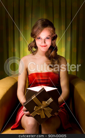 Magic gift box. stock photo, Beautiful young blond woman holding gift box in creative lighting. by exvivo