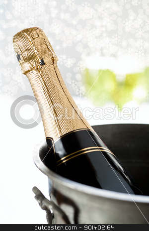 Champagne Bottle and Snow stock photo, Close up photograph of a champagne bottle on a blurry background by mpessaris