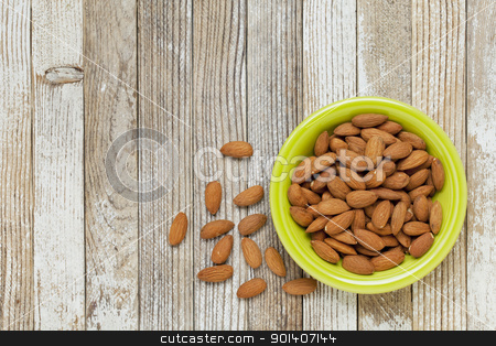 bowl of almonds stock photo, almonds in a ceramic bowl against grunge white painted wood table by Marek Uliasz