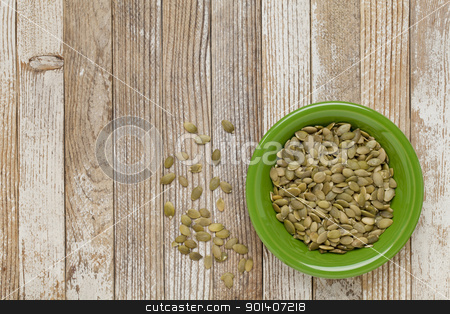 pumpkin seeds stock photo, pumpkin seeds in a green ceramic bowl on grunge white painted wood table by Marek Uliasz