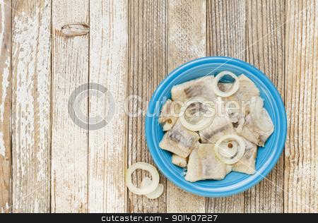 herring in wine with onion stock photo, herring in wine with onion and spices - blue ceramic bowl on grunge white painted wood table by Marek Uliasz