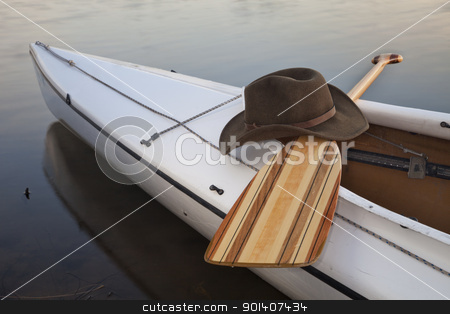 paddle, hat and canoe stock photo, a cowboy hat,a wooden paddle across cockpit of decked expedition canoe by Marek Uliasz