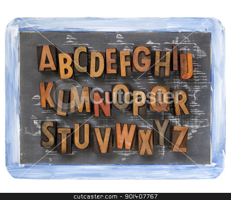 letterpress alphabet on blackboard stock photo, English alphabet - vintage wood letterpress printing blocks on a small slate blackboard with chalk texture and rough blue frame by Marek Uliasz