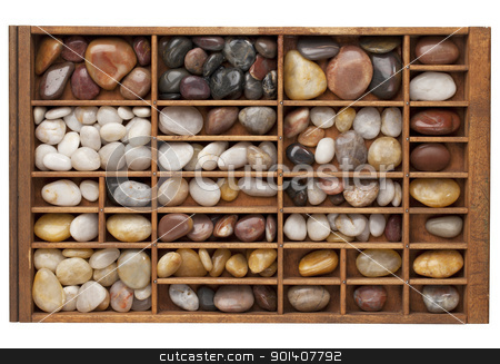 river pebbles in typesetter drawer stock photo, colorful river pebbles in vintage wood typesetter drawer isolated with clipping path by Marek Uliasz