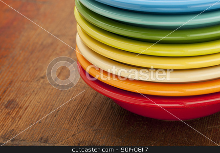 stack of colorful bowls stock photo, stack of colorful ceramic bowls against an old scratched wooden table surface by Marek Uliasz