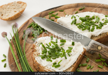 bread with cream cheese and chives stock photo, whole grain bread slices with cream cheese, green chopped chives. peeper and salt on a wood cutting board by Marek Uliasz
