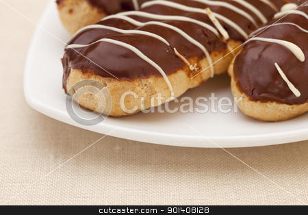 chocolate eclair pastry stock photo, choclate eclair pastry on white plate against tablecloth, shallow depth of field by Marek Uliasz