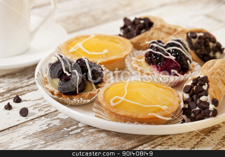 fruit mini tarts and coffee stock photo, plate of fruit mini tarts and coffee on a rustic wooden table by Marek Uliasz
