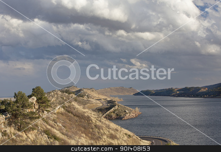 mountain lake in Colorado stock photo, Horsetooth Reservoir with Centennial highway near Fort Collins, Colorado, high wind conditions and heavy clouds in early spring by Marek Uliasz