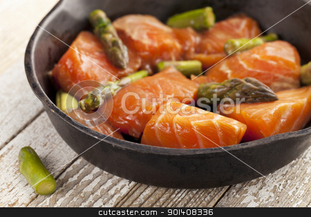 salmon and asparagus stir fry stock photo, salmon and asparagus stir fry in tamari sauce ready for cooking on iron pan by Marek Uliasz