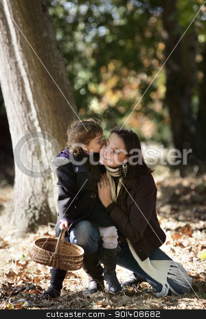 Little girl kissing her mum in woods stock photo, Little girl kissing her mum in woods by photography33