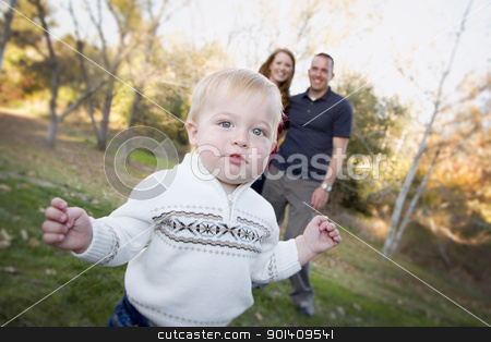 Cute Young Boy Walking as Parents Look On From Behind stock photo, Cute Young Boy Walking in the park as Parents Look On From Behind. by Andy Dean