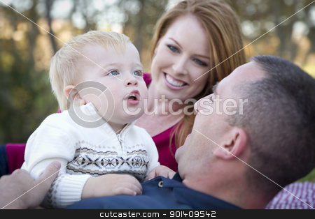 Cute Child Looks Up to Sky as Young Parents Smile stock photo, Cute Child Boy Looks Up to the Sky as Young Parents Smile. by Andy Dean