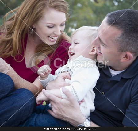 Attractive Young Parents Laughing with Child Boy in Park stock photo, Attractive Young Parents Laughing with their Child Boy in the Park. by Andy Dean