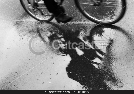 cyclist reflected in puddle in the rain stock photo, Cyclist reflected in puddle in the rain by anton havelaar