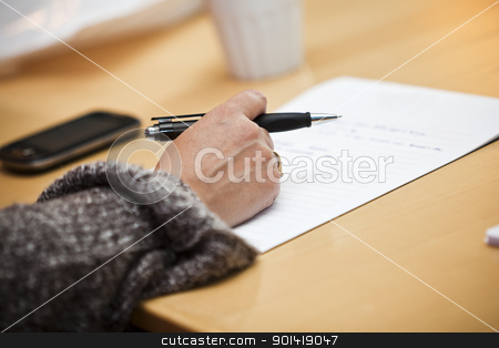 Hand with a pen stock photo, Human hand holding a pencil on a table by Anne-Louise Quarfoth