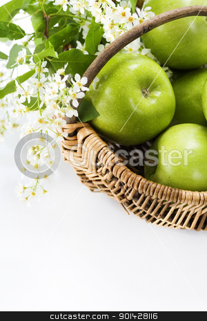 Green apple with flowers stock photo, Green apple with flowers in a basket on a white background by klenova