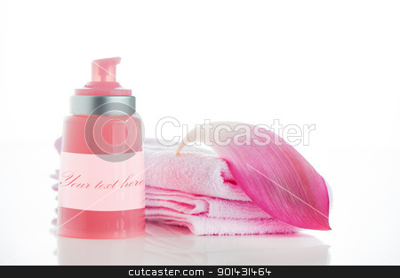 A pink towels with a lotus petal and a bottle of cosmetic on whi stock photo, A pink towels with a lotus petal and a bottle of cosmetic on white background and area for your text by p.studio66