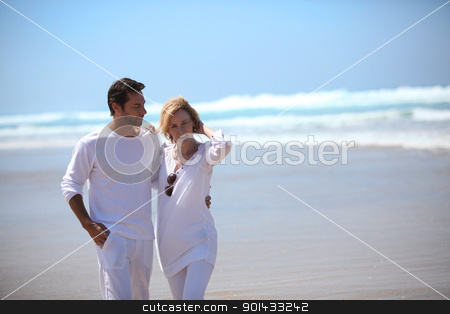 A couple walking on a beach and holding each other. stock photo, A couple walking on a beach and holding each other. by photography33