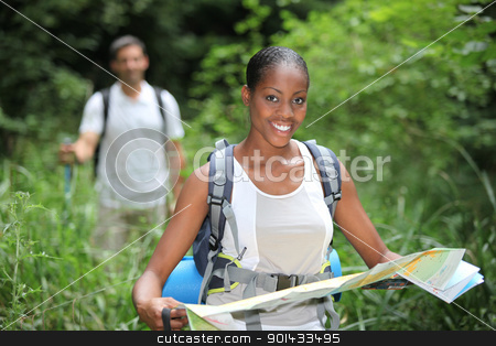 Woman map reading while hiking through long grass stock photo, Woman map reading while hiking through long grass by photography33
