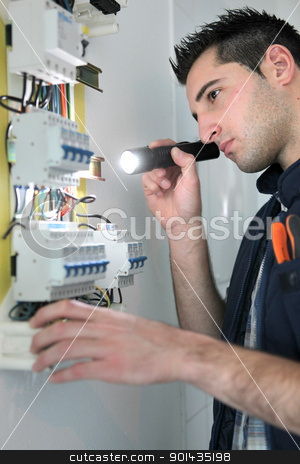 Electrician examining fuse box stock photo, Electrician examining fuse box by photography33