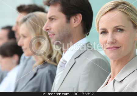 Businesswoman standing in a line with colleagues stock photo, Businesswoman standing in a line with colleagues by photography33