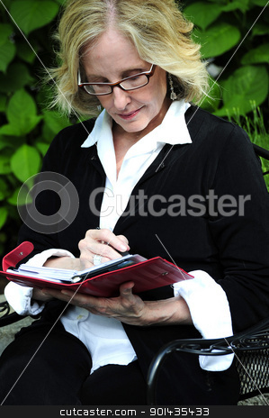 Business woman. stock photo, Business woman checking her appointment calendar. by OSCAR Williams