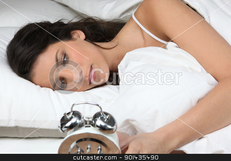 Woman looking her alarm clock stock photo, Woman looking her alarm clock by photography33