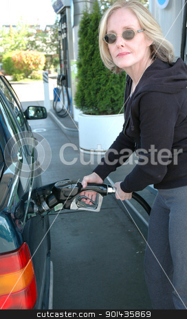 Pumping gas. stock photo, Mature female blond beauty pumping gasoline into her car. by OSCAR Williams
