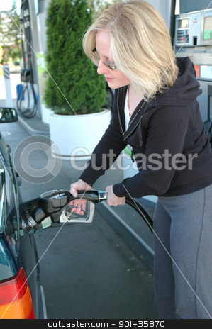 Female pumping gasoline. stock photo, Mature female blond beauty pumping gasoline into her car. by OSCAR Williams