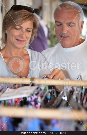 A middle age couple shopping for clothes. stock photo, A middle age couple shopping for clothes. by photography33
